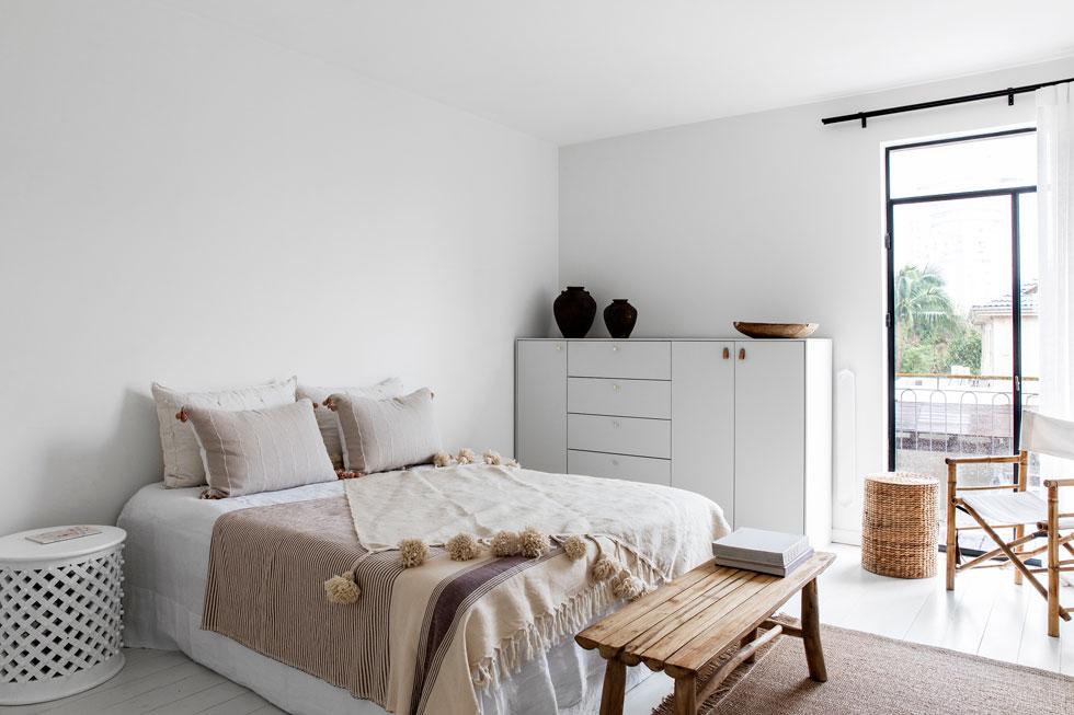 חדר הורים צחור לגמרי. הצבעוניות הטבעית נובעת מטקסטיל בגווני חום ובז' ומרהיטי העץ והנצרים (צילום: איתי בנית)