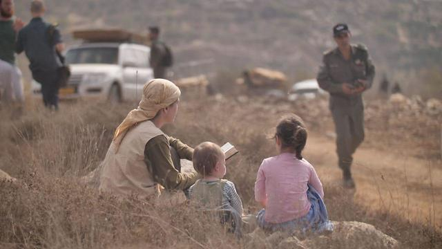 Yitzhar settlers look on at Israeli forces (Photo: Avraham Shapira)