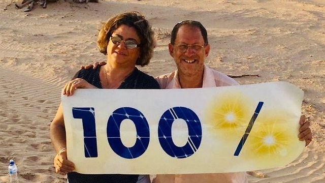 Dorit Banet and Yosef Abramowitz celebrate at one of their solar-panel fields in Israel's southern Arava region, which will be 100% solar-energy powered by next year
