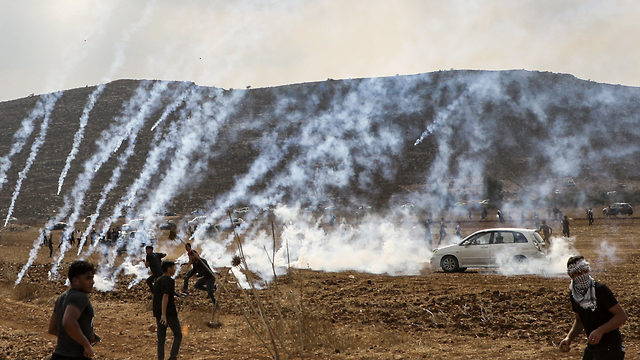 Tear gas fired by IDF troops falls among Palestinians protesting the construction of an outpost near the West Bank settlement of Shiloh, Oct. 17, 2019 (Photo: Getty Images)