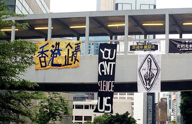 מימין: כרזת ''שלום'' עם אצבע משולשת, הכתובת ''אתם לא תשתיקו אותנו'', והכתובת ''הונג קונג נשארת מלוכדת''