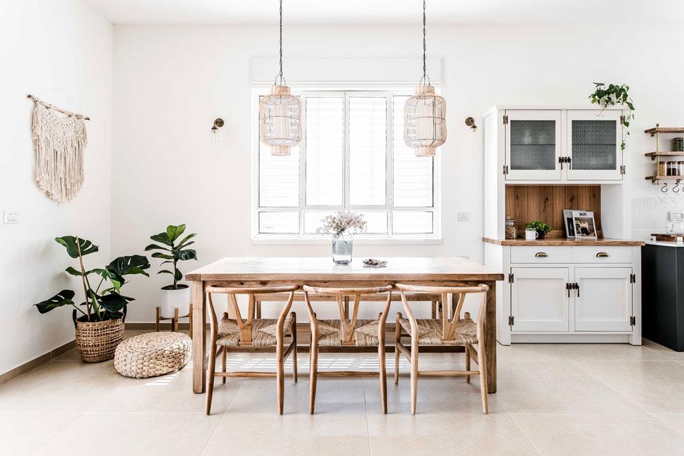 """שולחן אוכל מסיבי מעץ מוקף בכסאות מדגם שהפך לסמל לעיצוב הדני. """"היה כאן משחק של איזונים"""", אומרת המעצבת שיר שטייגמן, """"בין כפרי, וינטג' וסקנדינבי""""  (צילום: קרין רבנה)"""
