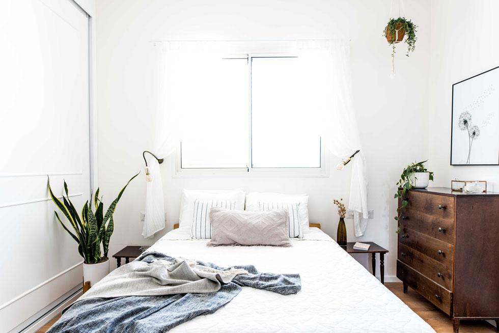 חדר ההורים צנוע בממדיו. שידת החתלה מעץ כהה משמשת לבגדים. שולחנות וינטג' הוצבו בצדי המיטה, והרהיטים הכהים בולטים על הרקע הלבן (צילום: קרין רבנה)