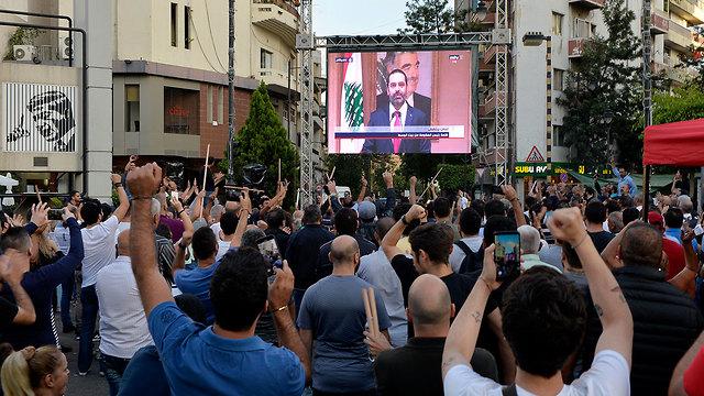 קהל צופה ב התפטרות של ראש ממשלת לבנון סעד אל חרירי ב ביירות (צילום: EPA)