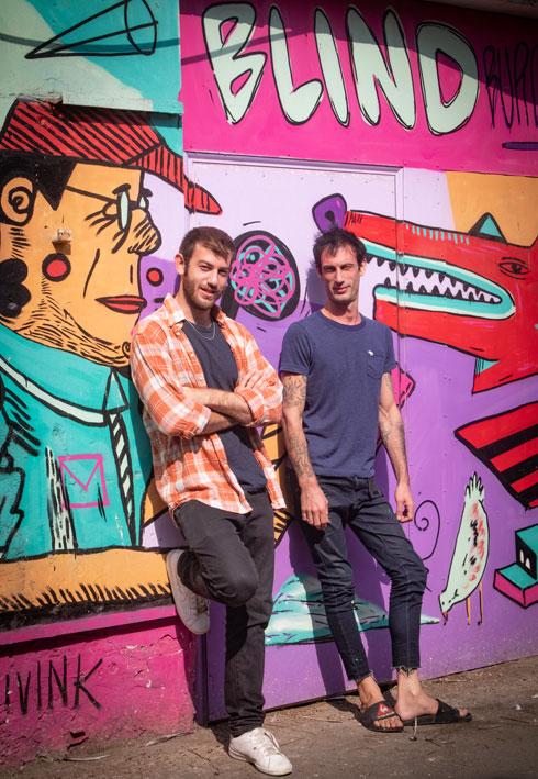 """זיו (מימין) וארז שמח על רקע ציור קיר שלהם. """"עליות וירידות קיצוניות"""" (צילום: גיל נחושתן)"""