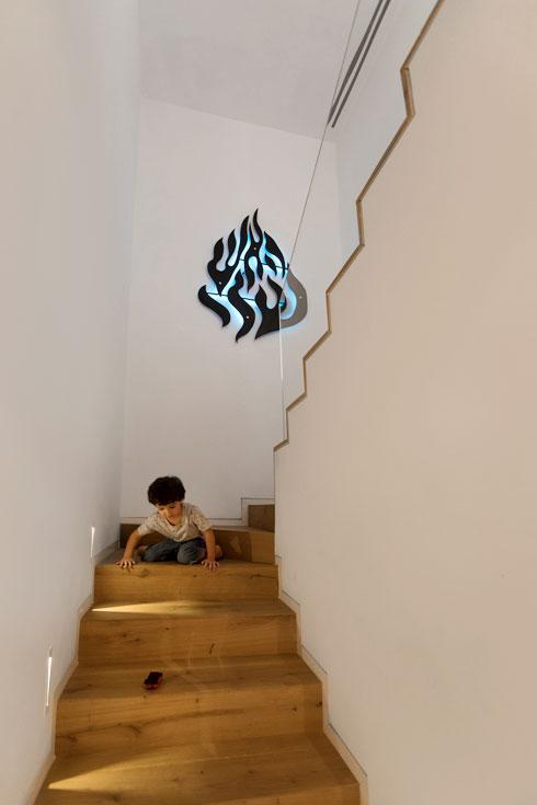 ההשתייכות הברסלבית משתקפת גם במדרגות היורדות לקומת חדרי הילדים, עם סמל ''האש שלי'' (צילום: שירן כרמל)