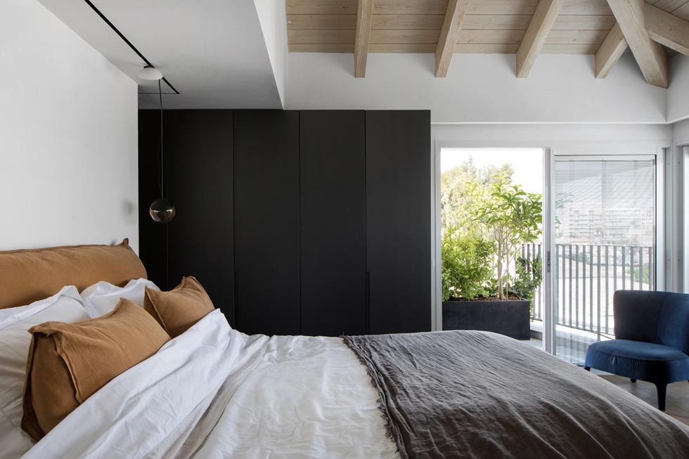חדר השינה פונה לנוף המוסכים של דרום פלורנטין, עטוף מרפסות משני כיוונים. הצמחייה מרככת את הנוף התעשייתי בצד הזה של הבית (צילום: שירן כרמל)