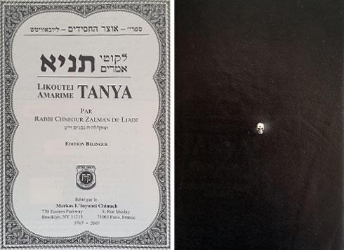 ספר התניא עטוף בכריכת עור שחורה (בצילום מימין), מנוקדת במרכזה בגולגולת קטנה, מוכספת כתכשיט (צילום: ענת ציגלמן)