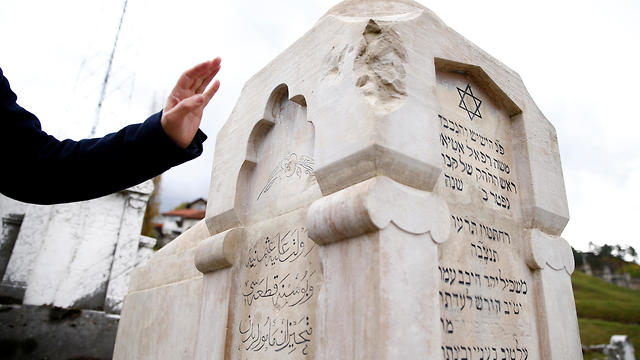 Eli Tauber shows a gravestone where the text is engraved in three languages on the resting place of a Jew whose real name is Mose Attias, known as Zeki Efendi Rafaelovic, at the Jewish cemetery in Sarajevo, Bosnia and Herzegovina, Nov. 6, 2019