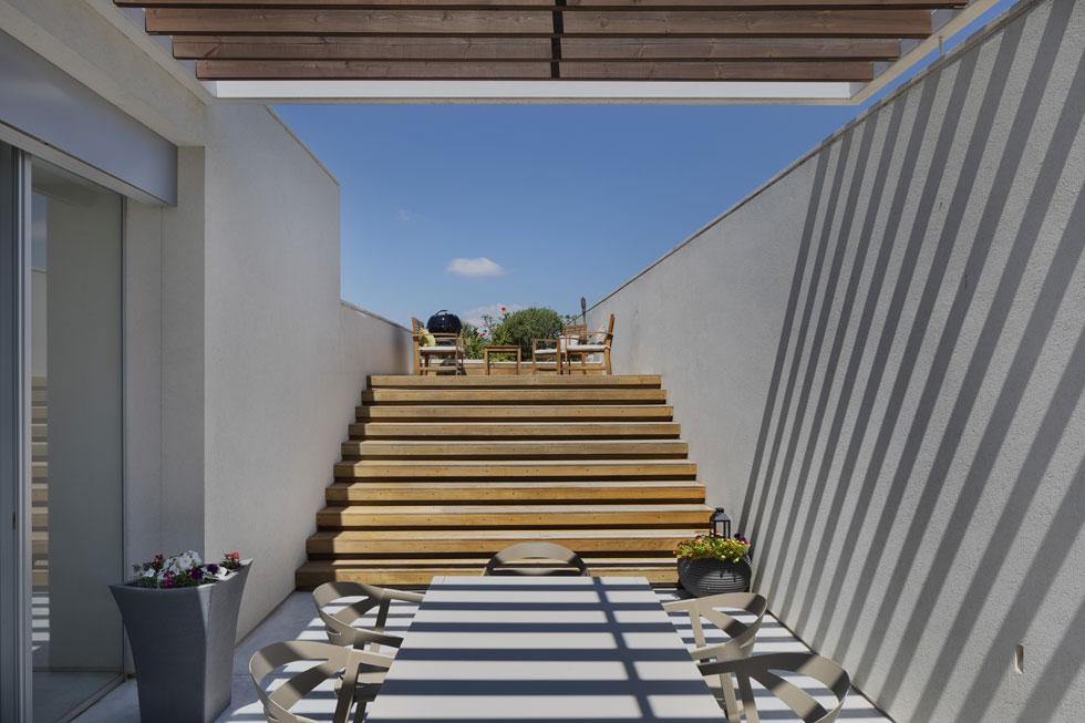 מדרגות עץ מובילות מפינת האוכל החיצונית אל מפלס הגג (צילום: אסף פינצ'וק)
