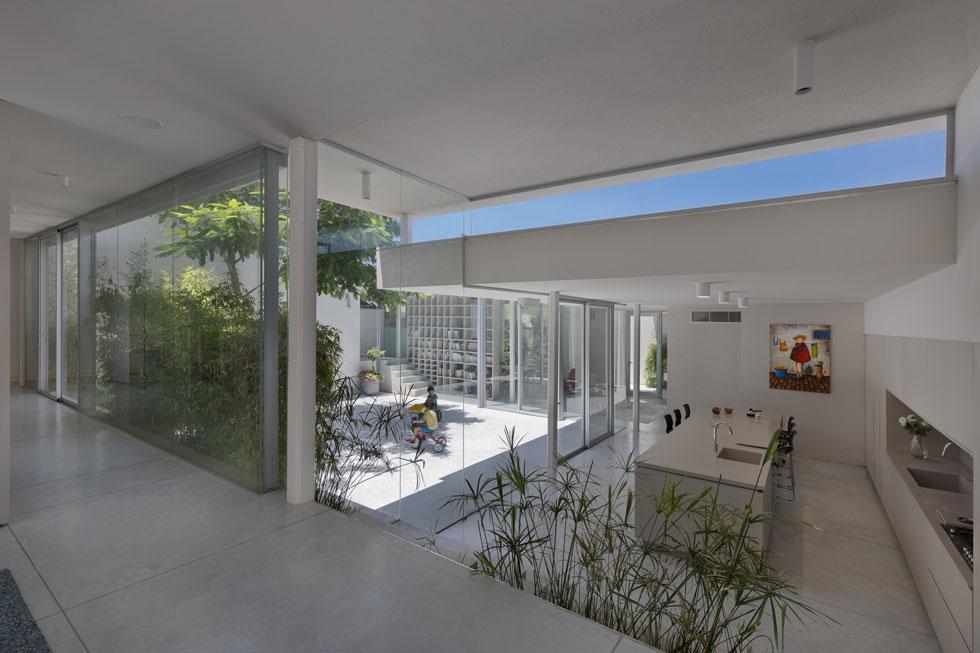 מלמעלה אפשר להשקיף על כל הבית. מסדרון שקוף משמאל מוביל אל החלק הפרטי, שבו 2 חדרי עבודה ו-3 חדרי שינה - להורים ולשני בניהם (צילום: אסף פינצ'וק)
