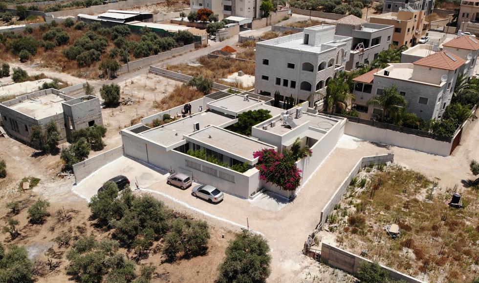 מבט מהאוויר. מהרחוב רואים רק חומה פשוטה שמקיפה את המגרש. הפתיחות היא כלפי פנים. ''הבית לא נועד לצטט את המבניות המסורתית הערבית'', מסביר האדריכל, ''אלא להעניק לערכים שבבסיסה פרשנות עכשווית'' (צילום: עמר ג'בארין)