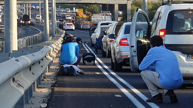 Israelis crouch by the side of the road as sirens sound in Rishon Lezion (Photo: Hasifa)