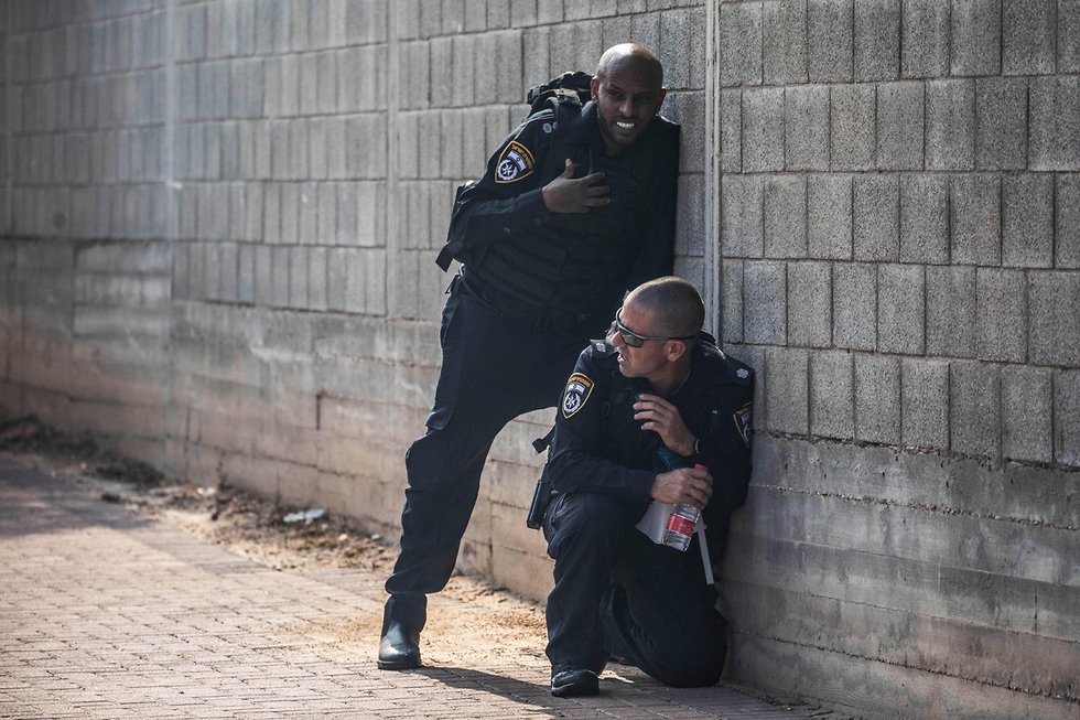 Policemen seeking cover during a rocket attack from the Gaza Strip on the city of Sderot (Photo: MCT)