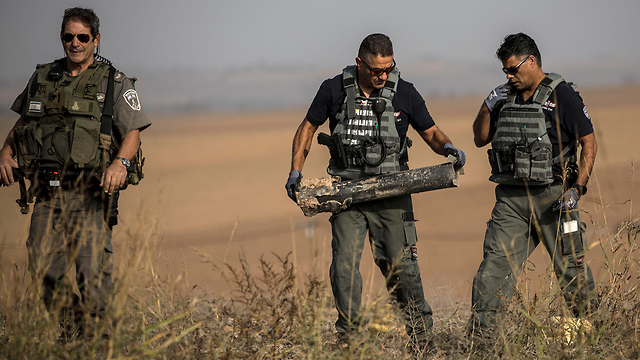 Security forces remove the remains of a rocket close to the Gaza border (Photo: AP)