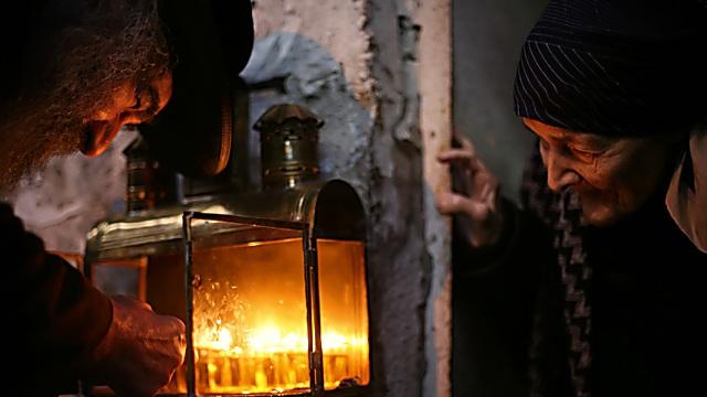 טרצ 13 – זוג קשישים במאה שערים בחנוכה, מדליק חנוכיה בפתח ביתם (צילום: אגניישקה טרצ'סבקה)