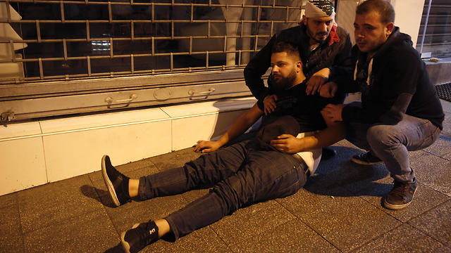 Anti-government protesters comfort their friend who fell from the tear gas, during a clash between supporters of the Shiite Hezbollah and Amal groups and the, in Beirut, Lebanon