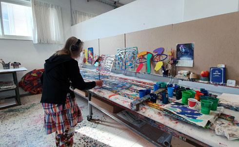 אסיסטנטים מציירים ביד את העבודות הגדולות יותר, לפי אבות טיפוס שגרשטיין מניח לפניהם (צילום: ענת ציגלמן)