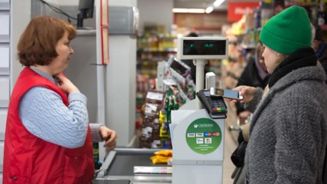 לקוחה משלמת בסמארטפון בסופר מקומי. בקרוב אצלנו? (צילום: בלומברג)