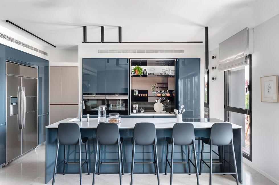בארונות המטבח שולב פיגמנט כחול. יפה מבשלת הרבה, ולכן המטבח עבר ללב הבית, עם אי עצום ושלושה תנורים (צילום: עודד סמדר)