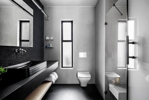 בחדר הרחצה הזוגי כיור שחור מונח על משטח אבן עם מדף עץ מרחף, על רקע קיר שכוסה אבן בזלת. ממול מקלחון רחב עם ספסל ישיבה בנוי  (צילום: איתי בנית)