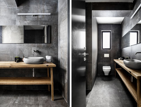 חדר הרחצה השני בדירה מכוסה באריחים דמויי בטון. מול שידת מדפי עץ פתוחה יש אמבטיה (צילום: איתי בנית)