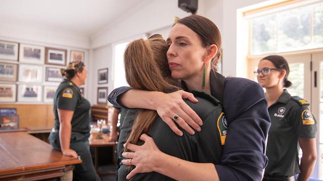 ג'סיקה ארדרן ראש ממשלת ניו זילנד עם אנשי הסיוע ש חילצו פצועים מ  האי הלבן הר געש התפרצות (צילום: EPA)