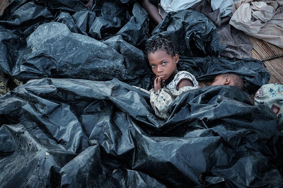 תמונות השנה AFP ילדים מתגוננים גשם מוזמביק שם מאות נהרגו בציקלון (צילום: AFP)