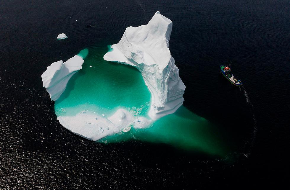 תמונות השנה AFP סירה חולפת על פני קרחון בקנדה  (צילום: AFP)