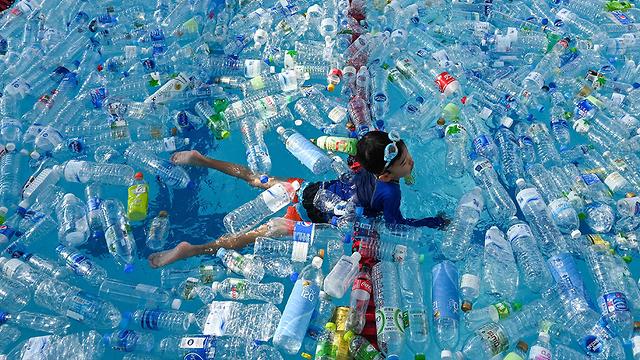 תמונות השנה AFP ילד בריכה בקבוקים יום מודעות לזיהום הימים בנגקוק (צילום: AFP)