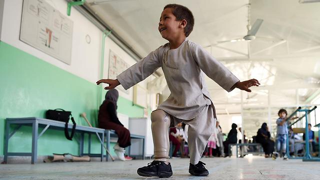 תמונות השנה AFP ילד אחמד סייד רחמן חוגג רגל תותבת נפצע מ כדור אפגניסטן (צילום: AFP)