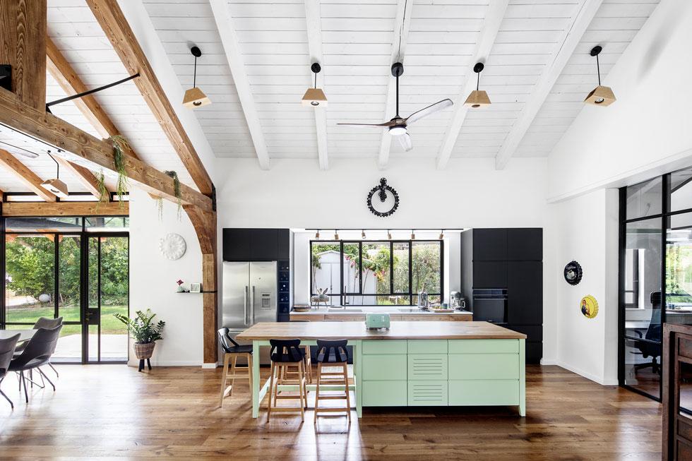 אי בצבע מנטה למטבח היה נקודת המוצא לעיצוב. מימין מציץ חדרון הזכוכית שנבנה לבעל הבית, המקיים שיחות ועידה בינלאומיות בשעות שונות (צילום: איתי בנית)