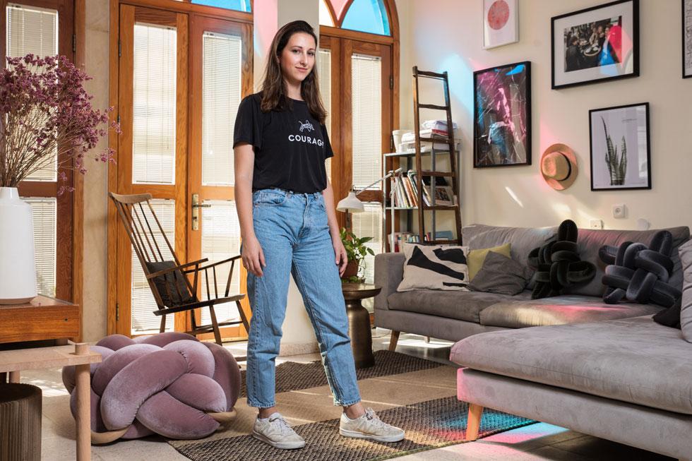"""נטע טסלר: """"בסלון יש לנו כמובן כריות קשר שלי: שתי כריות קשר על הספה בשביל הצבע והטקסטורה, וכרית ישיבה בצבע ורוד קטיפה במרכז הסלון שפשוט כיף לשבת עליה או להניח רגליים כשצופים בטלוויזיה"""" (צילום: טל שחר )"""