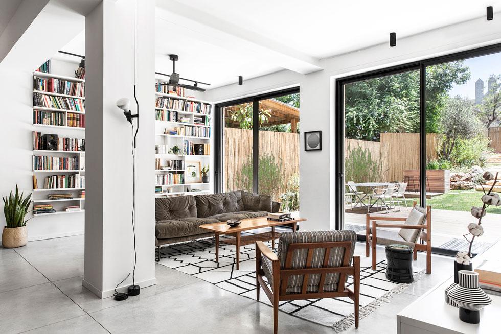 הסלון מוגדר באמצעות העמודים והקורות שמחברים בין הבית הישן לתוספת החדשה. אין בו תאורה מרכזית, אלא מנורות שיוצרות אווירה (צילום: איתי בנית)