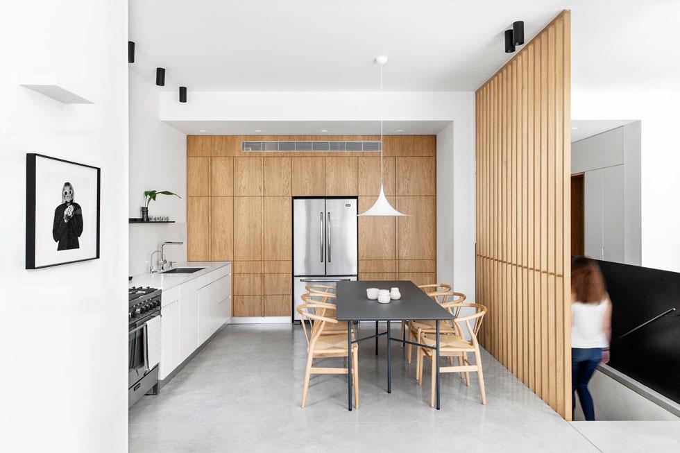 המטבח ופינת האוכל חולקים מרחב אחד. המדרגות תחומות בשתי מחיצות שונות: מצד אחד יריעת ברזל שחור, בצד השני מוטות עץ אנכיים  (צילום: איתי בנית)