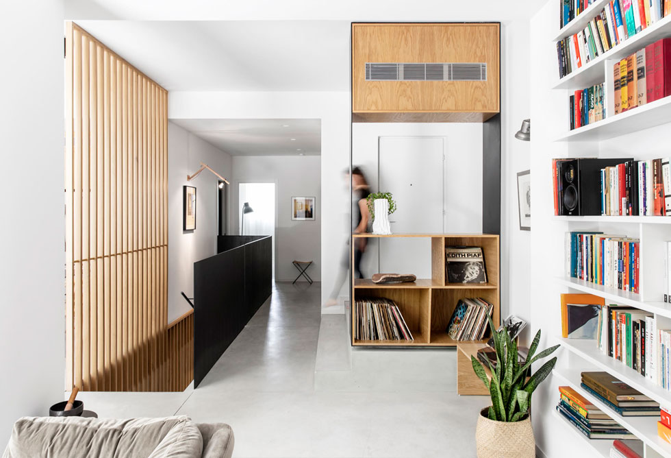 בכניסה לדירה, על במה מוגבהת מעט, הותקן רהיט דו צדדי שימושי. הרצפה הונמכה במכוון, כדי להשיג עוד גובה תקרות ולהכניס פנימה יותר אור (צילום: איתי בנית)
