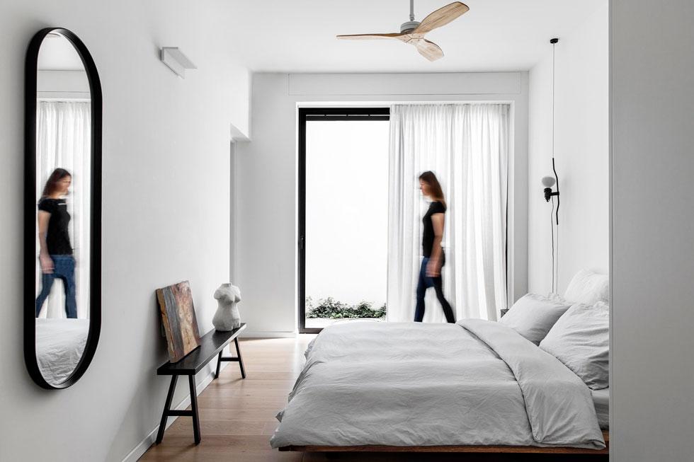 חדר ההורים מתאפיין במיעוט חפצים. למרות הקיר החוסם נכנס פנימה אור טבעי רב (צילום: איתי בנית)