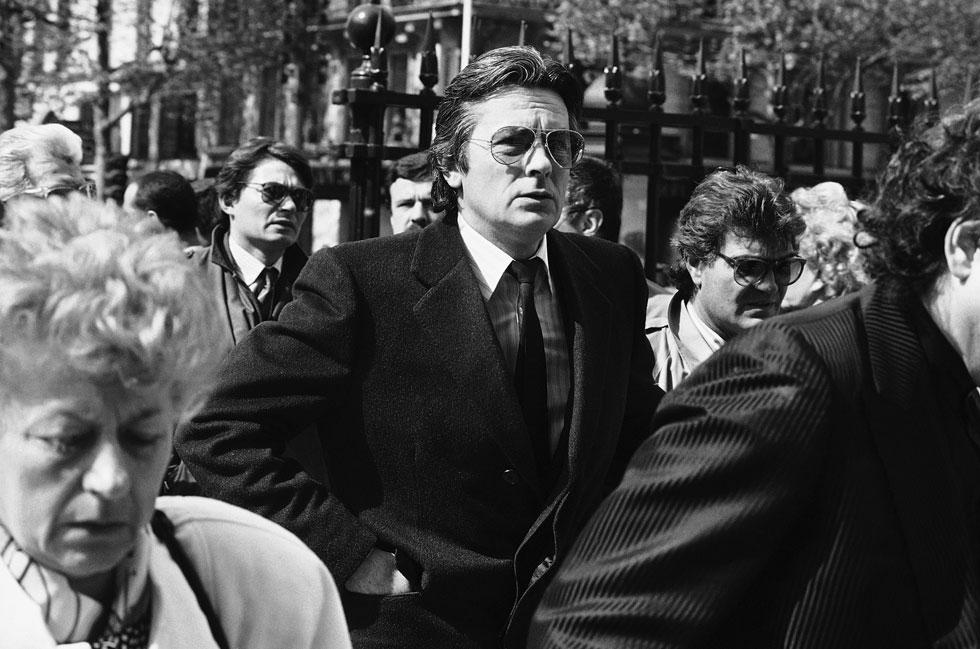 """כוכב הקולנוע אלן דלון מגיע להלווייתה של דלידה, 7 במאי 1987. למטה: הלהיט המשותף שלהם, """"פארולה, פארולה"""" (מימין) וסרטון המסקר את ההלוויה (צילום: AP)"""