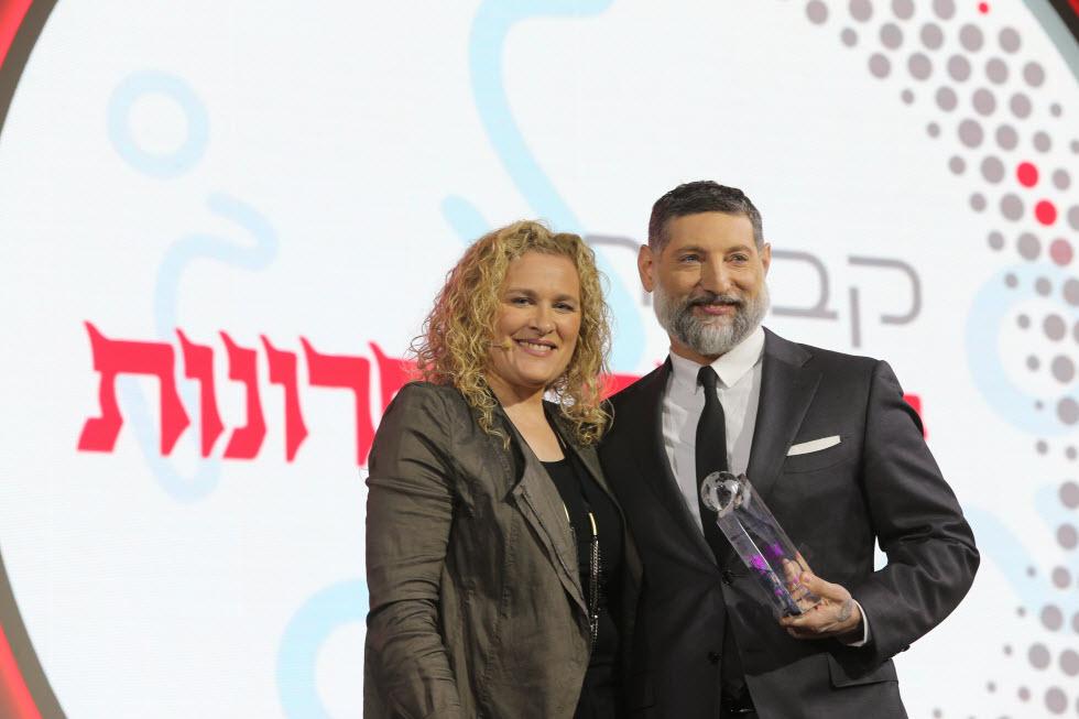 אסף גרניט מקבל את הפרס מג'ואנה לנדאו  (צילום: אלכס קולומוי)