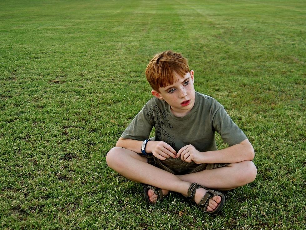 ילד אוטיסט בוהה בדשא  (צילום: shutterskock)