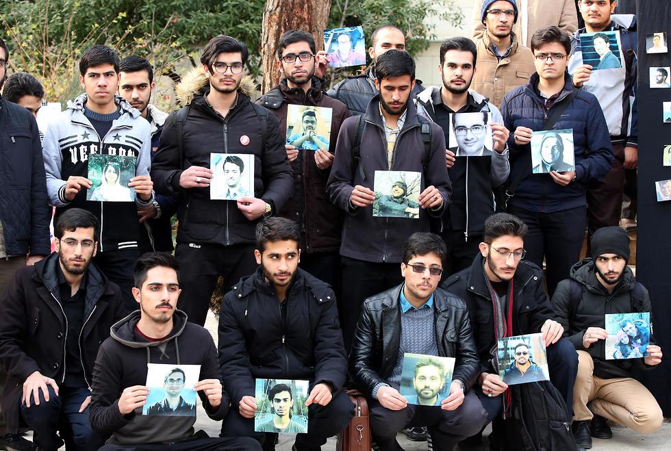 סטודנטים איראנים מציגים את תמונות הנספים באסון הפלת המטוס האוקראיני (צילום: EPA)