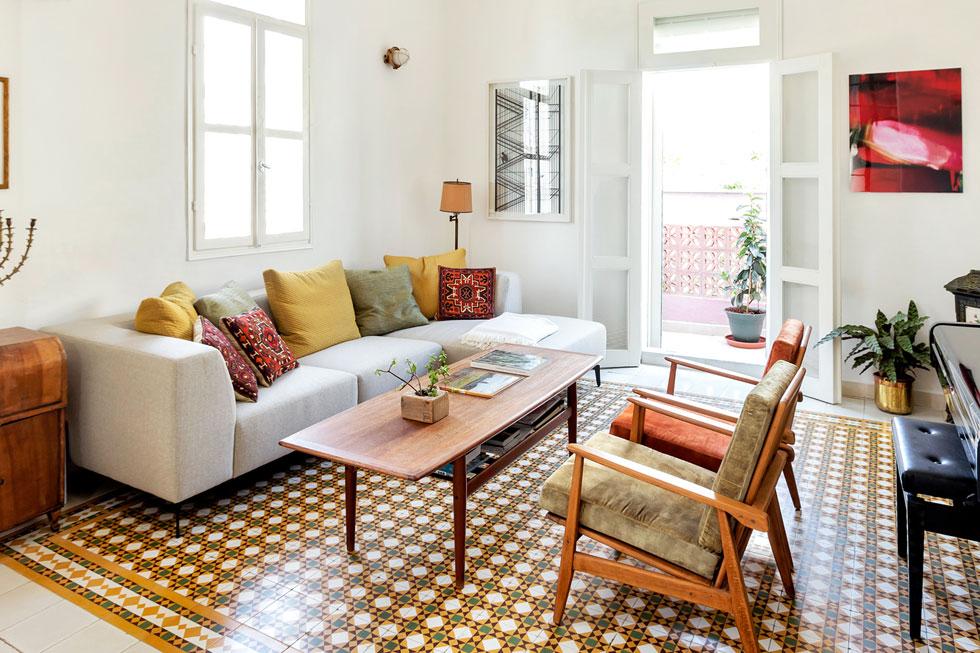 הסלון מוגדר בשטיח המרצפות המקוריות. הספה חדשה, הכורסאות ושולחן הקפה הם פריטי וינטג' ששופצו, ועל הקיר עבודה של מרב כהן בשחור-לבן (צילום: סוזי לוינסון)