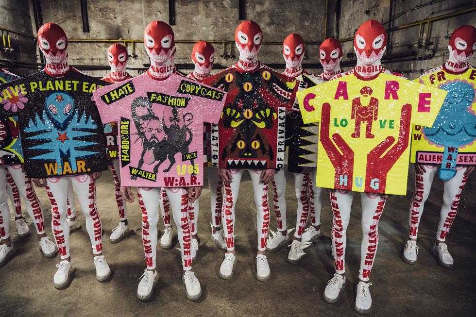 המעצב הבלגי וולטר ון בירנדונק הוא איש של הצהרות. הפעם ניצל את המסלול להעברת שלל מסרים: משמירה על כדור הארץ ועד ביקורת נגד העתקות בתעשיית האופנה. פניהם של הדוגמנים כוסו במסכות בד, ואת המסרים הם לבשו מעל חולצות בדו-ממד שנראו כשלטים (צילום: Francois Durand/GettyimagesIL)