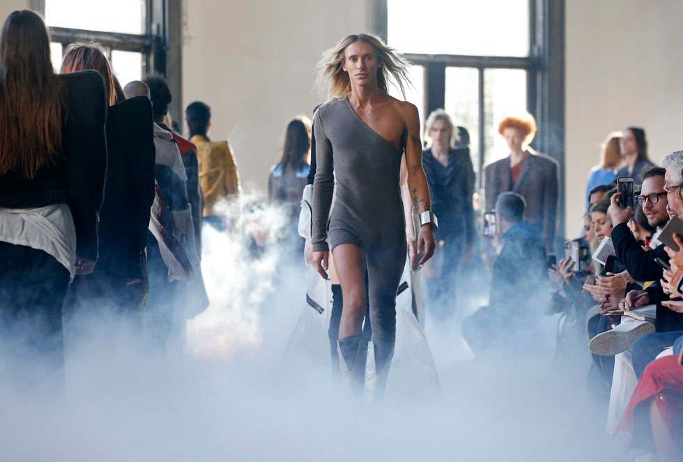 """המעצב ריק אוונס הציג את אחת הקולקציות החדות בעיצובו, אשר ממשיכה למתוח גבולות בסוגיות הרות גורל כמו גבריות, נשיות ומיניות. חדי העין לא יכלו לפספס על המסלול מעין """"כפילים"""" של המעצב, כמו דוגמן עם שיער בלונדיני ארוך לבוש אוברול א-סימטרי, שנראה כאילו נשלף ממסיבת דיסקו בסבנטיז (צילום: Thierry Chesnot/GettyimagesIL)"""