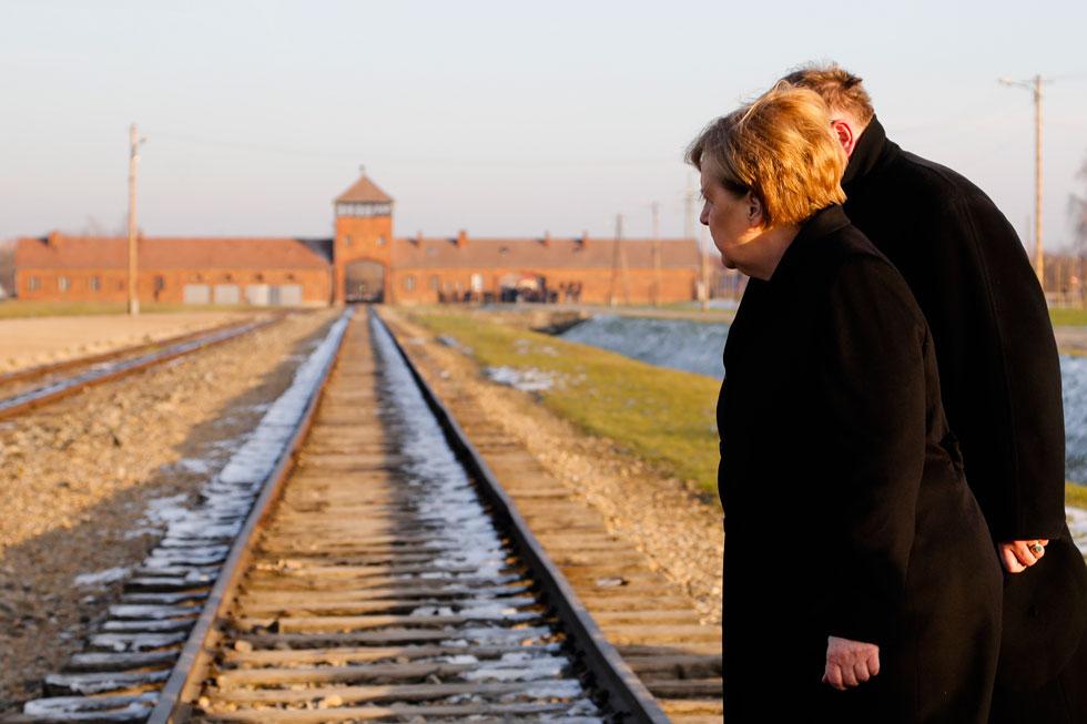 """מרקל עם המנהל של מוזיאון אושוויץ, פיוטר ציבינסקי, ליד פסי הרכבת בבירקנאו. """"יש לשמר את המקום הזה. גרמניה תרים תרומה משמעותית"""" (צילום: AP)"""