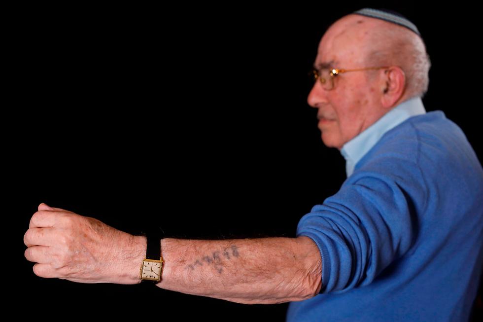 ניצול שואה שמול איצ'ק אושוויץ (צילום: AFP)