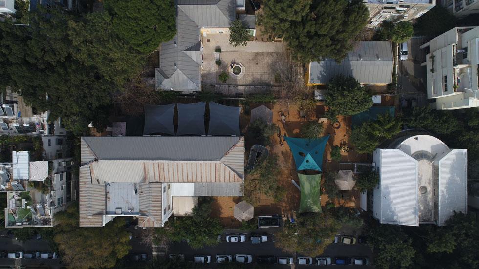 אשכול הגנים הראשון של לב ת''א (משמאל), לצד המרכז לתושבים ותיקים ע''ש צוקר. אם המאבק של ההורים ייכשל, פי שניים ילדים יחלקו את שליש פיסת החצר שתישאר (צילום: Drone Image Bank)