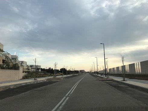 כביש הגישה לשכונה מלווה בשביל אופניים ובקיר אקוסטי, להגנה מפני שקשוקי הרכבת (צילום: מיכל בלאו)