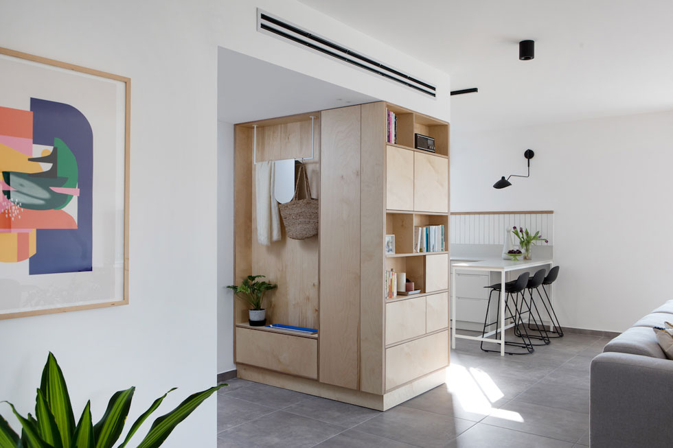 האלמנט הבולט בדירה היא קופסת נגרות רב צדדית מעץ ליבנה (בירץ'). מצד אחד היא יוצרת מבואה ומשמשת את הבאים, אל הסלון היא מפנה ספרייה, ומהצד השלישי היא הופכת לארונות המטבח הגבוהים, שעוטפים את המקרר (צילום: שירן כרמל)