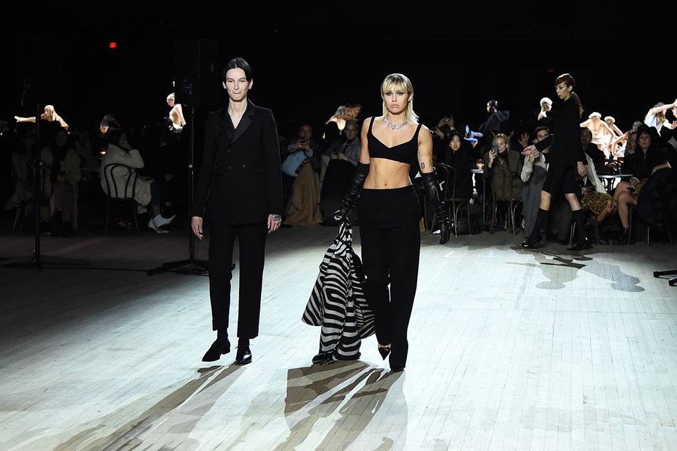 הזמרת מיילי סיירוס חתומה העונה על פתיחת וסגירת שבוע האופנה. בשבוע שעבר היא התייצבה בשורה הראשונה של טום פורד בלוס אנג'לס, אמש היא צעדה על המסלול של מארק ג'ייקובס בניו יורק. גם הפעם היא עשתה זאת במערכת לבוש שחורה שכללה מכנסיים בגזרה רפויה, חזייה שחורה וזוג כפפות עור  (צילום: Jamie McCarthy/GettyimagesIL)